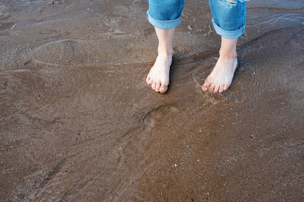 Feet on the beach in sunny summer day