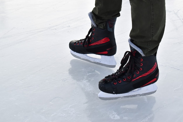 Feet in black men's skates stand on the ice. winter entertainment ice rink.