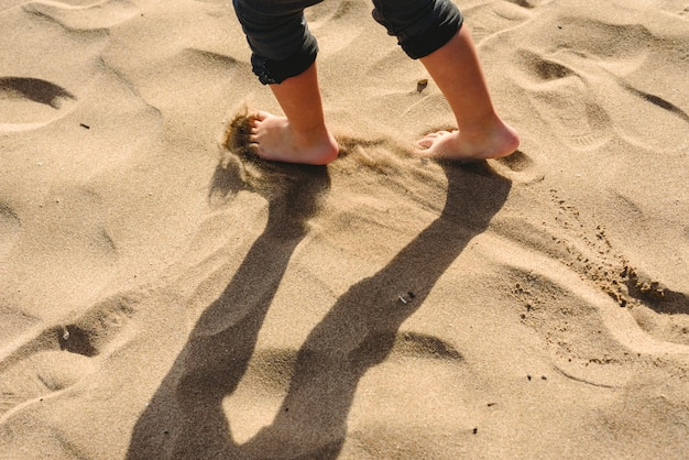Feet of boy walking on the sand of the beach.