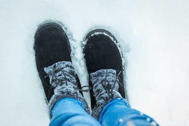 The feet of a child in blue jeans and warm boots on the snow. beautiful and practical women's winter shoes.