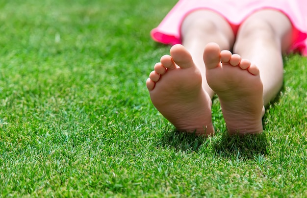 Feet of a child on the lawn on the grass