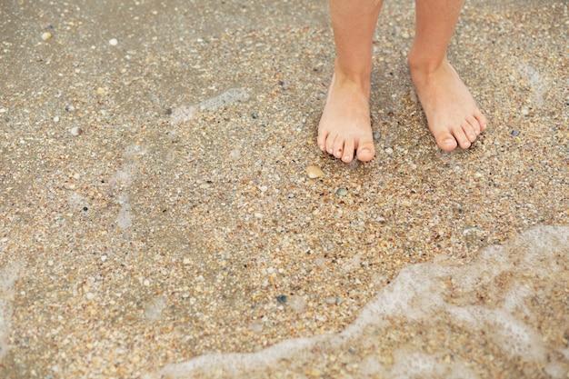 Ноги ребенка на песчаном пляже с ракушками