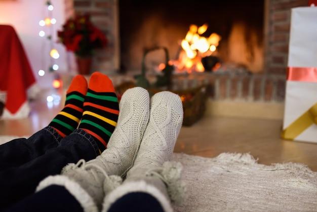 Feet in christmas socks near fireplace