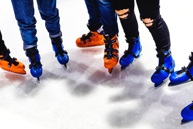 Feet closeup of group of friends ice skating together