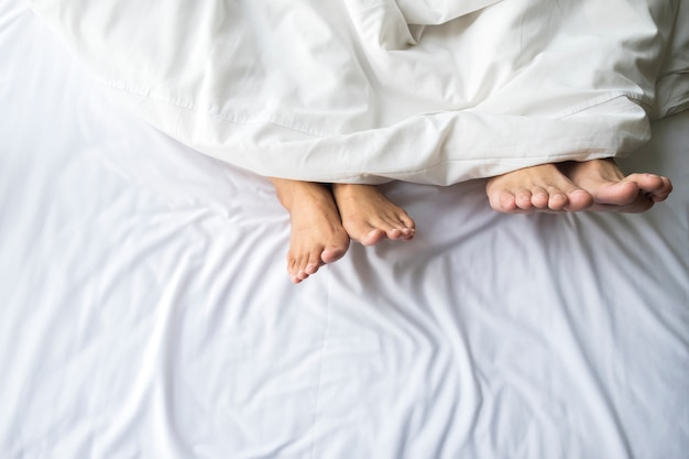 Feet of couple in comfortable bed.