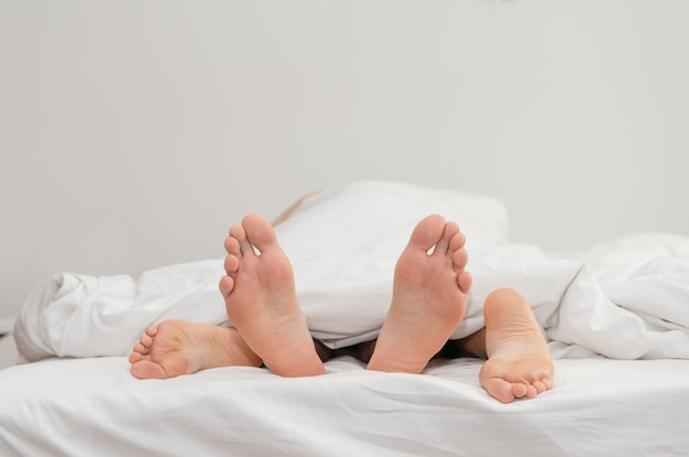 Feet of couple in love on the bed having sex under white blankets