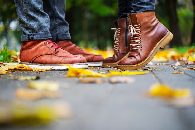Feet of a couple in love in brown shoes on the path of the autumn park, strewn with fallen leaves. girl stands on toes. kiss concept