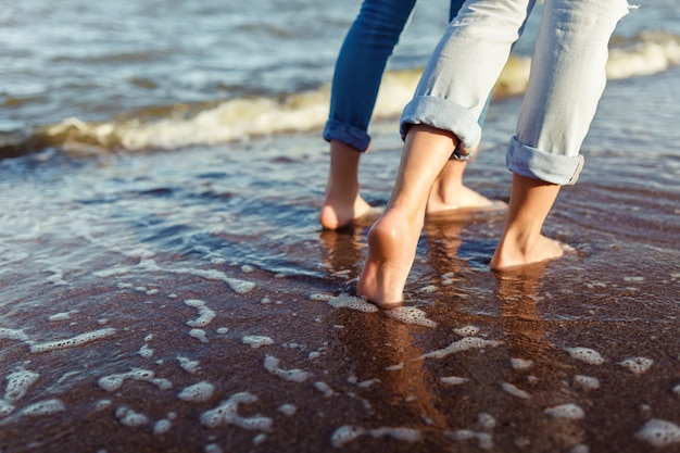 Feet of couple woman and man in the sea waves
