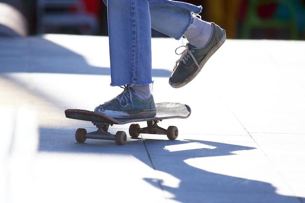 街でスケートボードをしている足の女の子