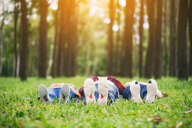 Feet of a group of young people while lying down on a green grass in the forest