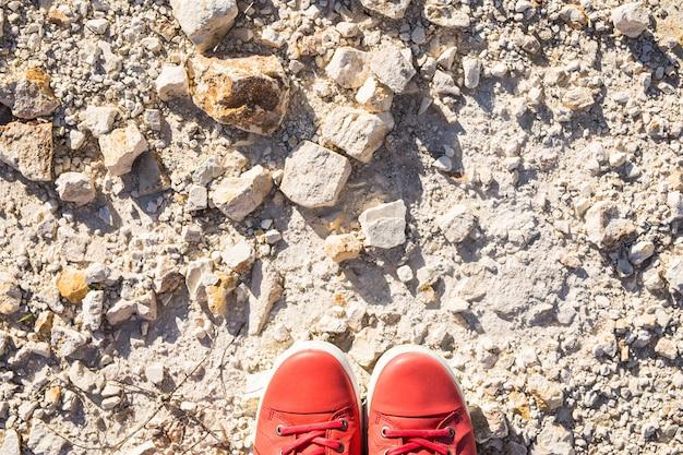 石の背景にカジュアルなピンクの靴の足。