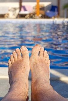 オープンプールの青い水の前の足