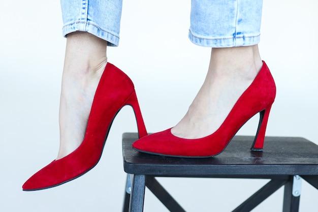 白い背景の上のジーンズと赤いヒールの靴の足