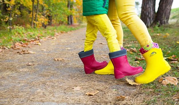 秋の森の母と娘の赤と黄色のゴム長靴の足。季節性、季節、落ちた乾燥したカエデの葉、家族の散歩、愛とケアの気持ち、親子関係