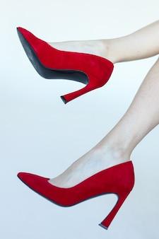 白い背景の上の赤いかかとの靴の足