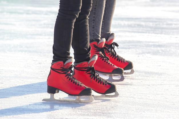 아이스 링크에서 빨간색 스케이트에 발. 취미와 여가. 동계 스포츠