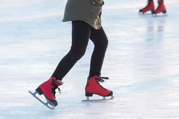 아이스 링크에서 빨간색 스케이트에 발. 취미와 스포츠. 휴가 및 겨울 활동.