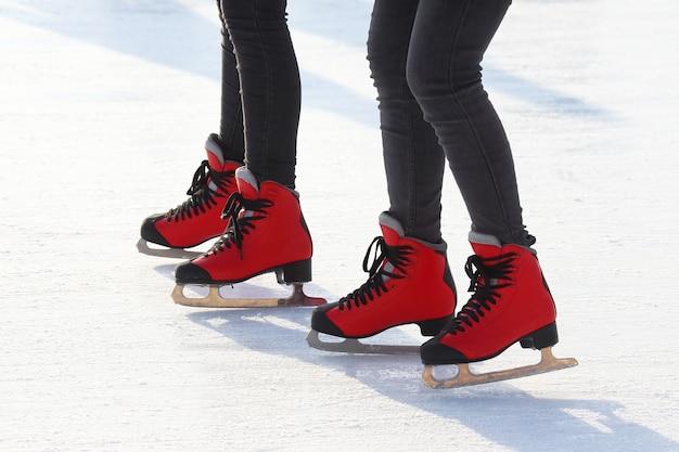 Ноги в красных коньках на катке