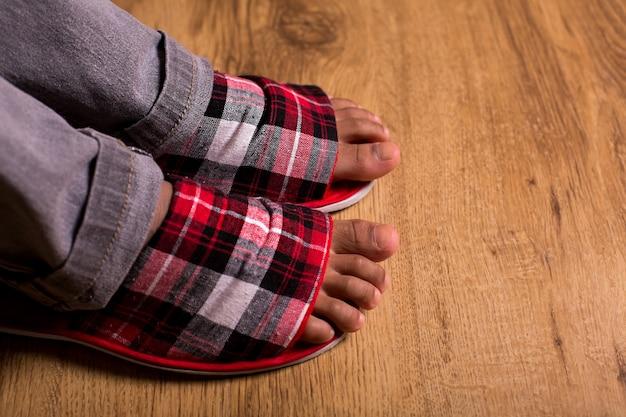 슬리퍼와 바지에 발은 회색 바지에 체크 무늬 슬리퍼가 절대적으로 편안한 느낌을줍니다.