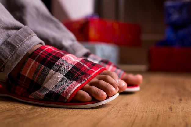 아이의 발 옆에 선물 상자 옆에 슬리퍼에 발은 아침 놀람이 기다리고 있습니다 ...