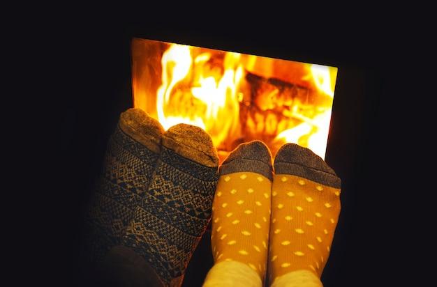 居心地の良い火で暖まるカップル愛好家のウールの靴下の足