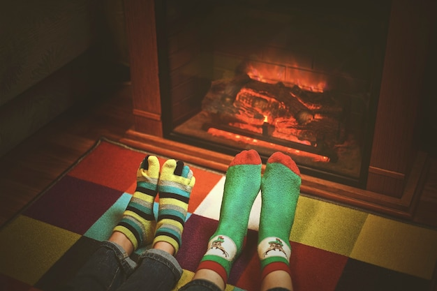 クリスマスの暖炉のそばのウールの靴下の足。足でクローズアップ。冬とクリスマスの休日のコンセプト。