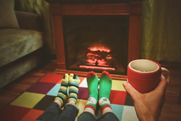 クリスマスの暖炉のそばのウールの靴下の足。女性は温かい飲み物を飲みながら暖かい火でリラックスし、羊毛の靴下で足を温めます。足でクローズアップ。冬とクリスマスの休日のコンセプト。