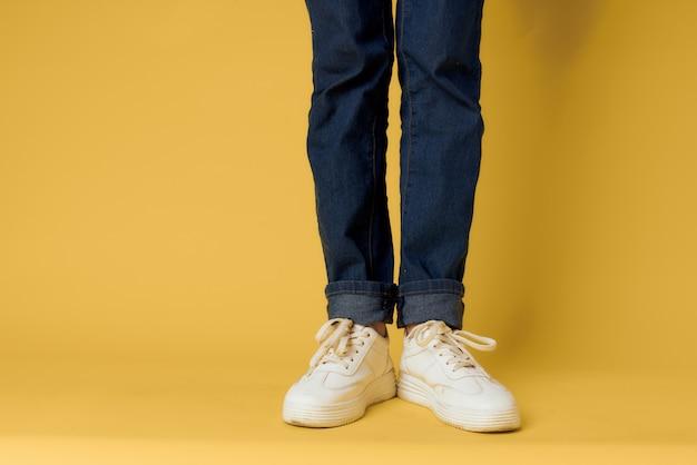 足ジーンズファッション靴白いスニーカー黄色の背景。高品質の写真