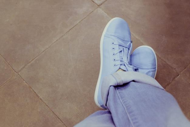 Feet jeans sneakers floor