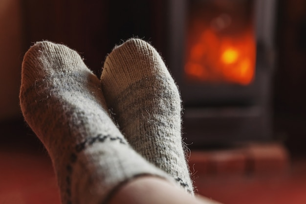 Feet legs in winter clothes wool socks at fireplace background woman sitting at home on winter or autumn evening relaxing and warming up winter and cold weather concept hygge christmas eve
