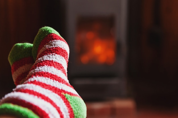 Feet legs in winter clothes wool socks at fireplace at home on winter or autumn evening relaxing and warming up