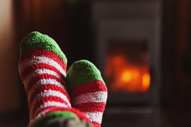 Feet legs in winter clothes wool socks at fireplace