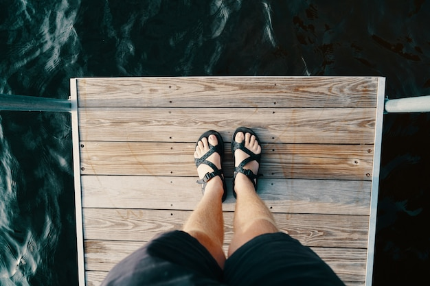 Feet of a male standing on a wooden surface over the body of water
