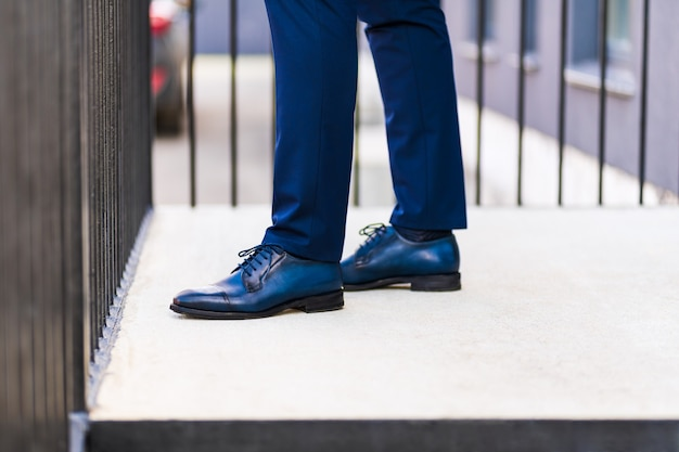 Feet of a man in a blue suit and blue shoes on the porch of a house on the street.
