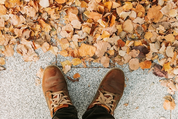 The feet of a man in brown boots on the gray granite sidewalk