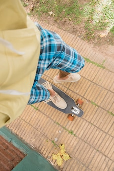 Feet of man standing on longboard