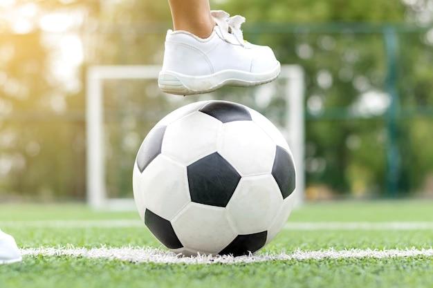 Ноги мальчика в белых кроссовках, наступающего на футбольный мяч посреди футбольного поля.