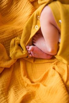 오렌지 배경에 신생아의 발. 매크로