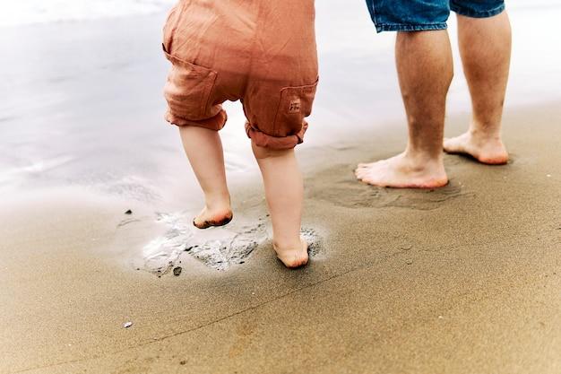 海岸で父親の隣にいる3歳の少年の足