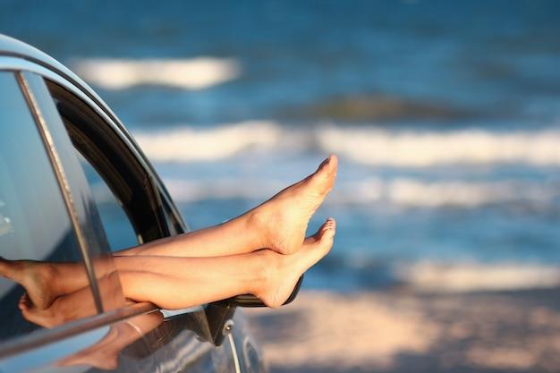 ビーチの車の窓に女性の足