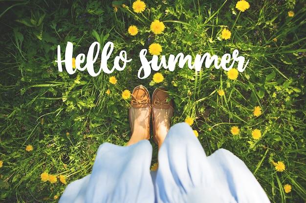 Ноги женщины на зеленой траве и желтых цветах, надпись привет лето