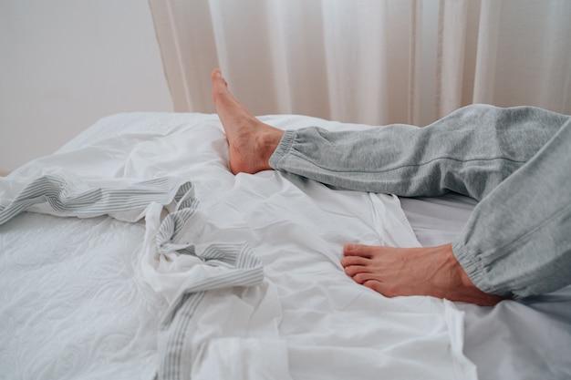 편안한 침대에 알아볼 수 없는 사람의 발