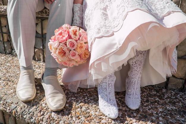 新郎新婦のウェディングシューズの足ピンクのバラのウェディングブーケ