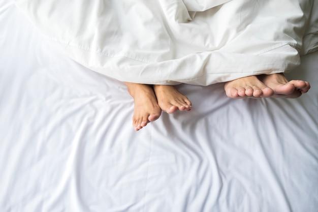 快適なベッドでのカップルの足。