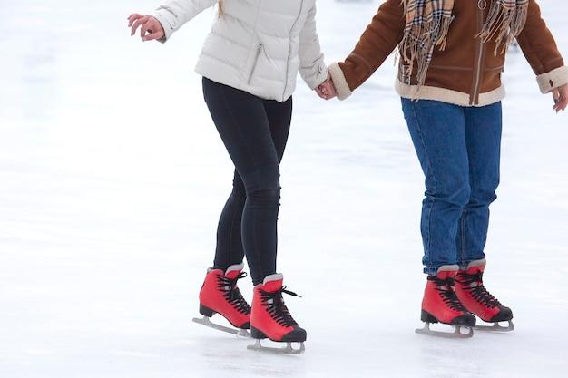 아이스 링크에서 스케이트를 타는 다른 사람들의 발. 취미와 여가. 동계 스포츠