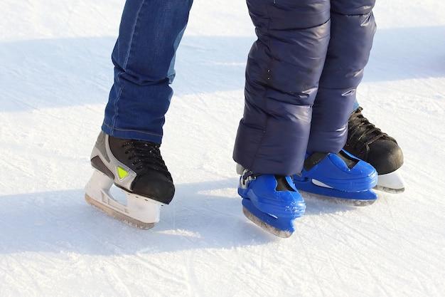 アイススケートリンクでスケートをしているさまざまな人々の足