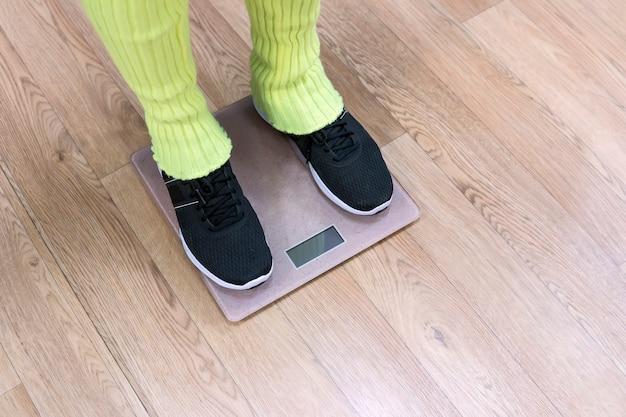 저울에 서 있는 레그워머와 트레이너를 착용한 피트니스 여성의 발. 운동 후 체중을 확인하기 위해 저울 위에 서 있는 운동화를 신고 여성 다리를 봅니다. 운동 후 체중 감량.