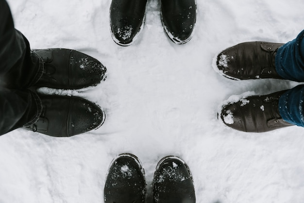 Ноги четырех человек в снегу крупным планом
