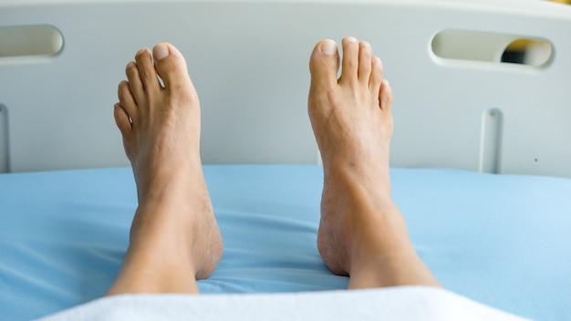 Ноги пациента на кровати в больничной палате. понятие синдрома гийена-барре и болезни онемевших рук или побочного эффекта вакцины.