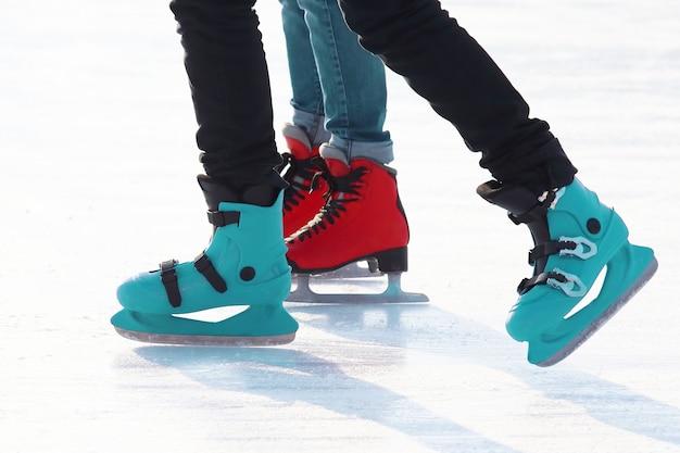 거리 아이스 링크에서 스케이트를 타는 사람들의 발. 스포츠 및 엔터테인먼트. 휴식과 겨울 방학.
